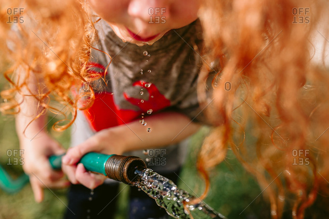 Child drinking from hose
