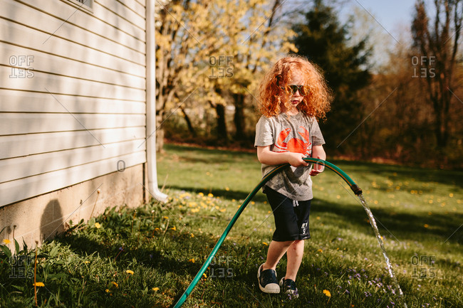 Child playing with hose in yard