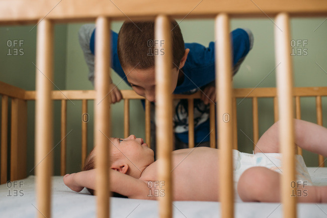 Big brother looking at baby sister in her crib