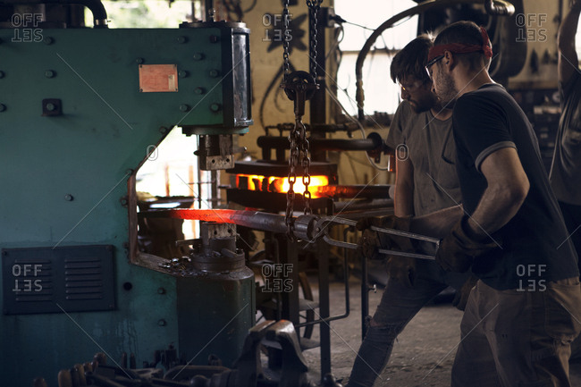 Blacksmiths forging rod in machinery at workshop