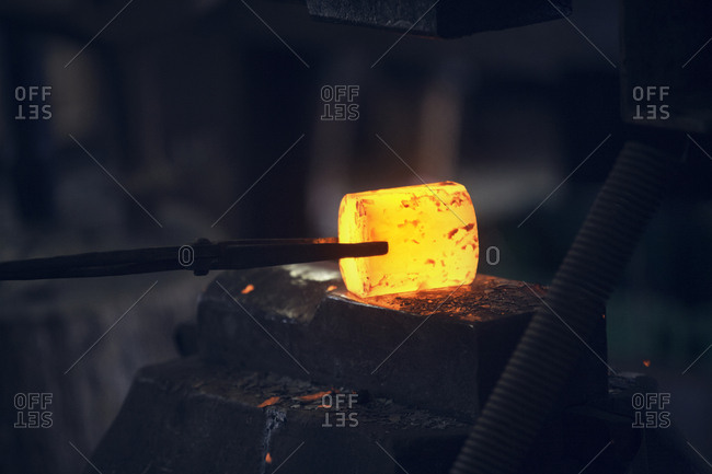 Glowing heated metal held by tongs in metal industry
