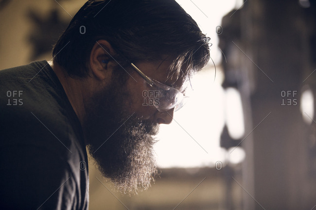 Close-up of blacksmith wearing protective eyewear working in workshop