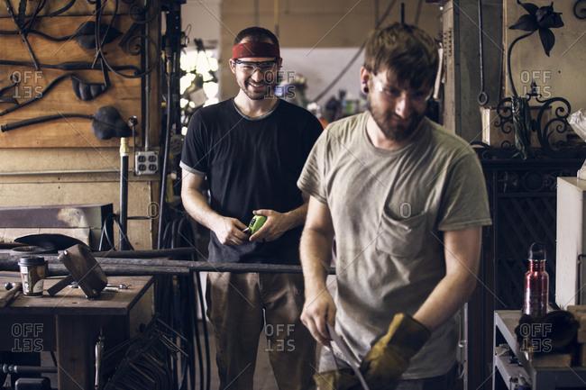 Smiling coworkers standing in workshop