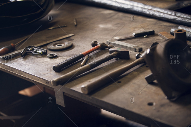 High angle view of work tools on table at blacksmith shop