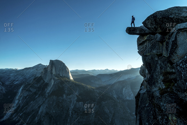 Low angle view of man standing on mountain at Yosemite National Park against clear blue sky