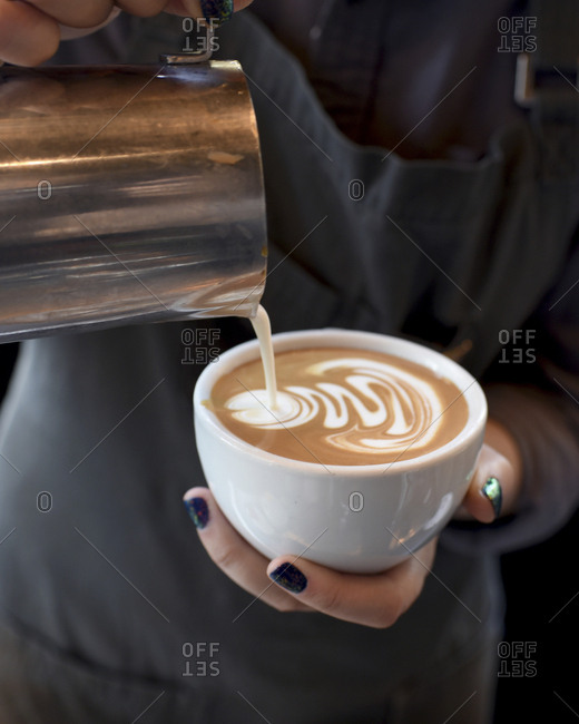 Midsection of female barista pouring cream in coffee at cafe