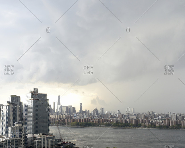 New York, USA - September 14, 2016: Modern buildings by Hudson river against cloudy sky during sunset