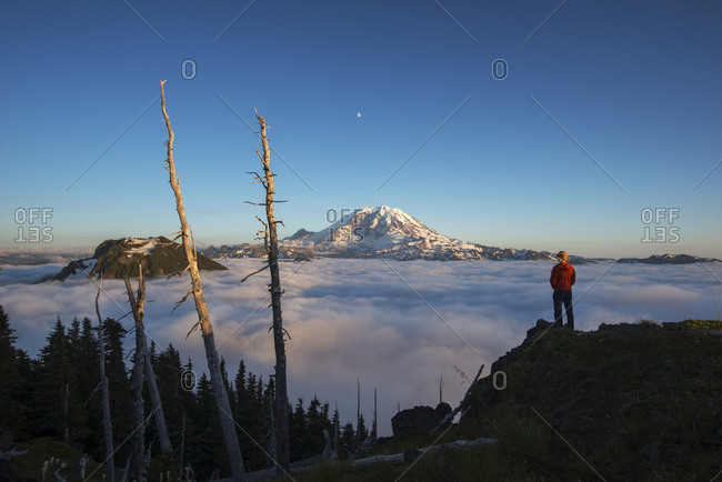 Rear view of male hiker standing on mountain by cloudscape during sunrise