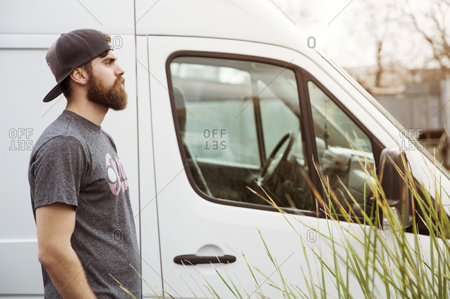Side view of man looking away while standing by pick-up truck