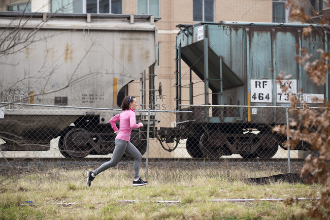 Side view of woman jogging on grassy field by freight train