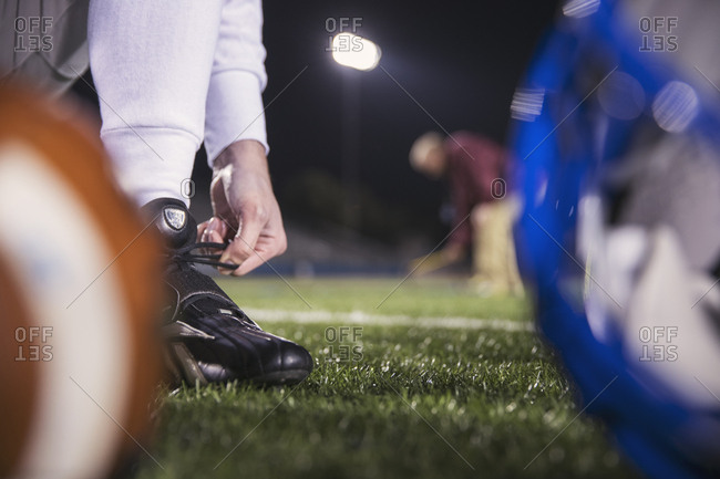 Low section of American football player tying shoelace on field with coach in background