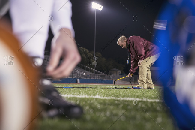 American football coach placing agility ladder on turf at stadium
