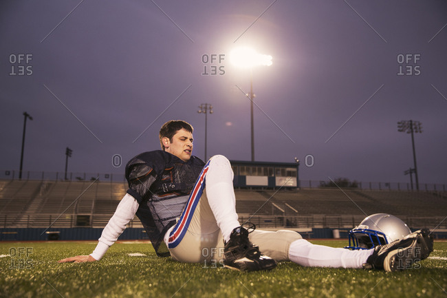American football player relaxing on grassy field at stadium against sky