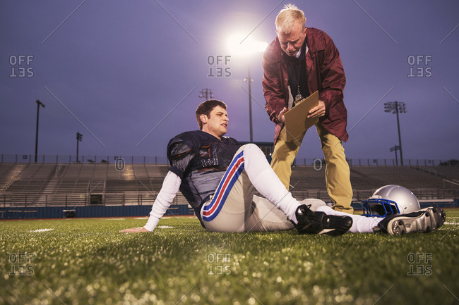 Coach showing clipboard to tired American football player relaxing on field at stadium