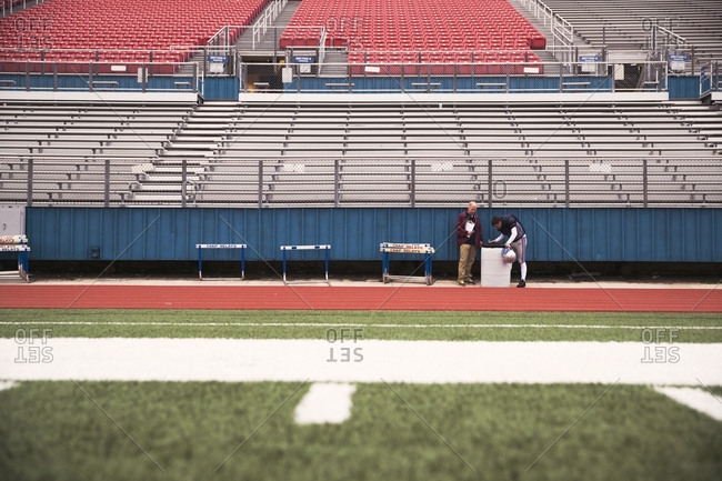 Mid distance view of Coach and American football player at stadium