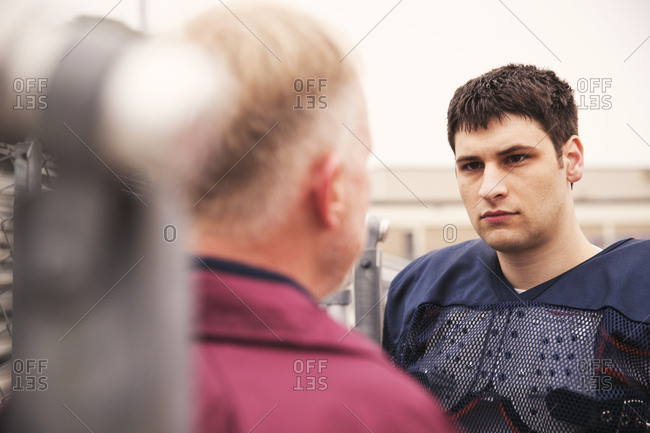 Coach discussing with American football player at stadium