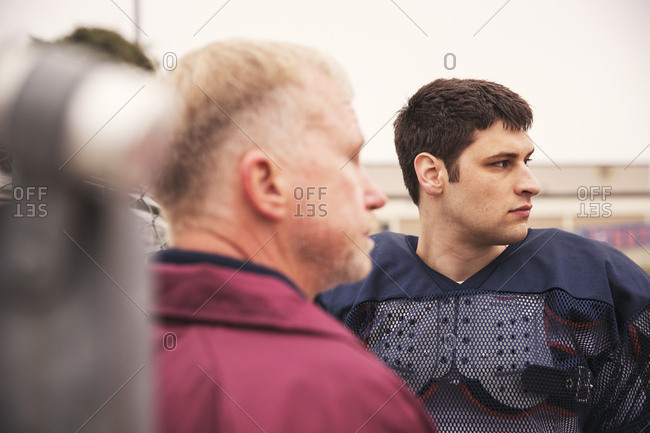 Coach and American football player looking away while standing at stadium
