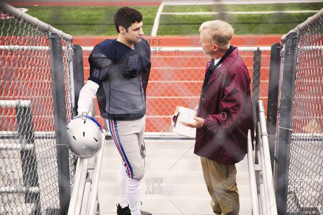 High angle view of coach discussing with American football player at stadium