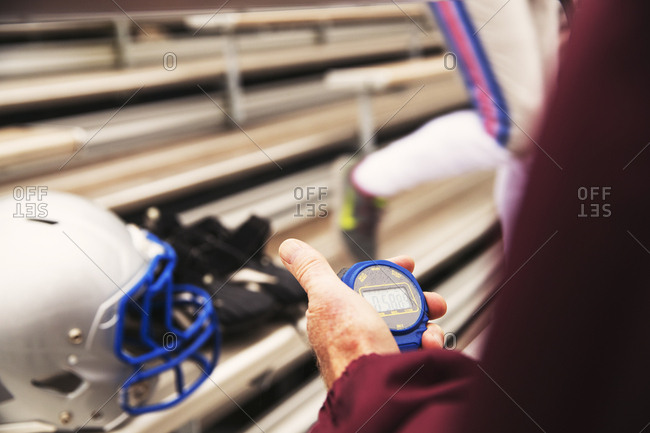 Cropped hand of American football coach holding stopwatch at stadium