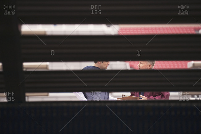 Coach discussing with American football player at stadium seen through bleachers
