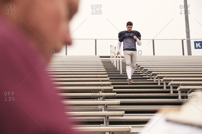 Coach holding clipboard while American football player exercising in stadium