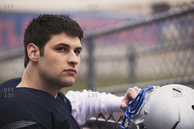 American football player looking away while standing by fence in stadium