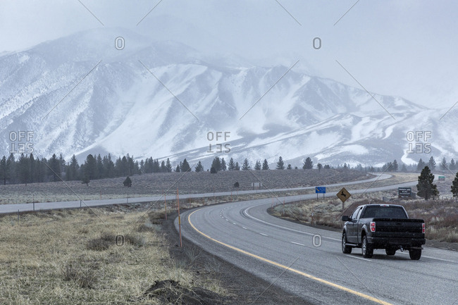 Pick-up truck on road leading towards snowcapped Mammoth Mountain