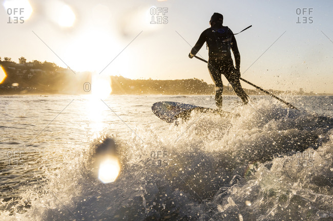 Rear view of man holding pole while surfing in sea during sunset