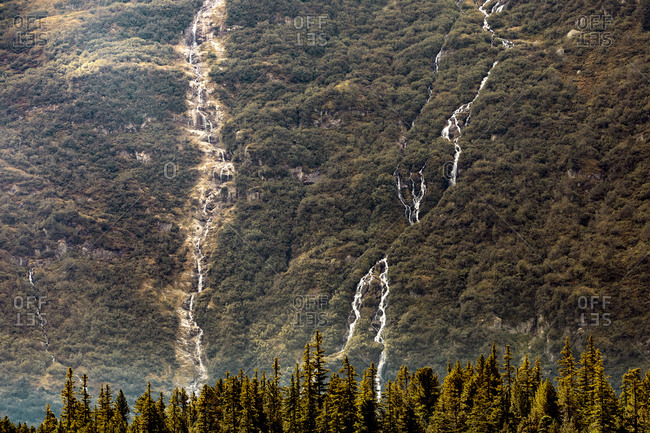 Distant view of waterfalls on green mountain
