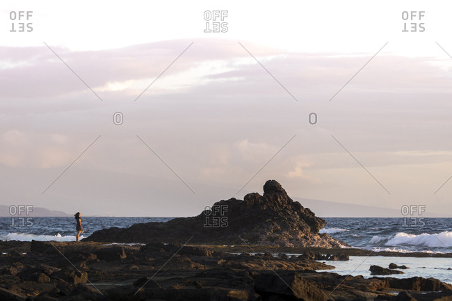 Distant view of woman standing on rock by sea against cloudy sky