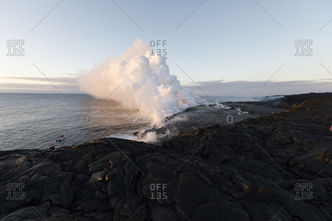 Smoke emitting from volcano at shore against sky