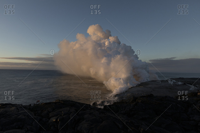 Smoke emitting from volcano at beach against sky during sunset