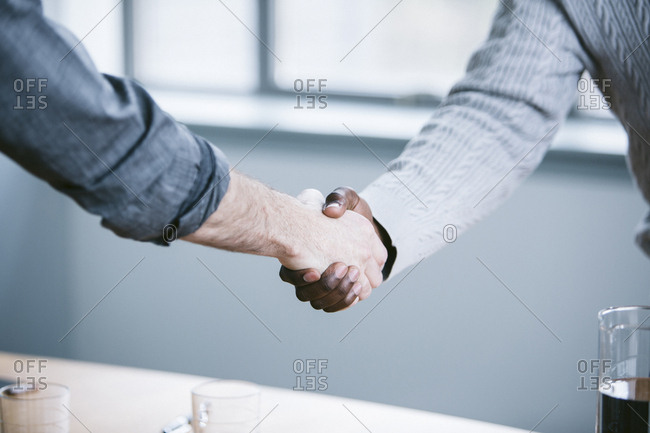 Midsection of businessmen handshaking in board room