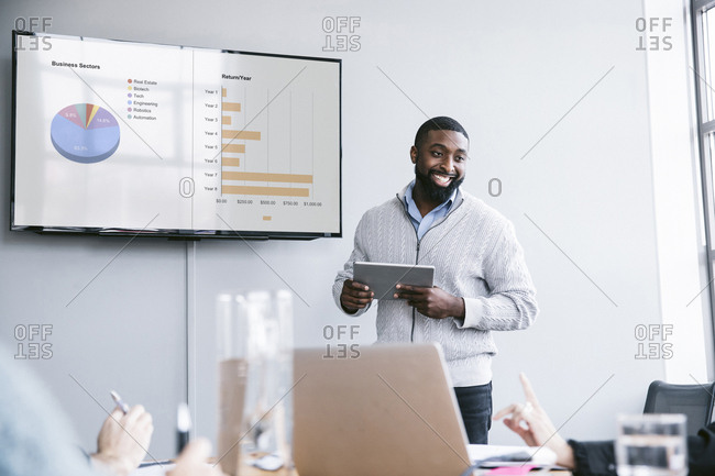 Smiling businessman holding tablet computer explaining graphs in meeting at board room
