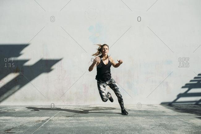 Dedicated female athlete exercising on sidewalk against white wall