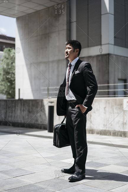 Full length of thoughtful businessman standing on bridge