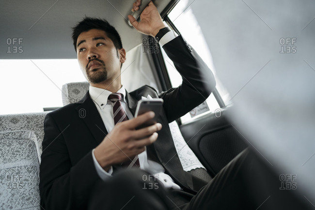 Thoughtful businessman holding smart phone while sitting in taxi