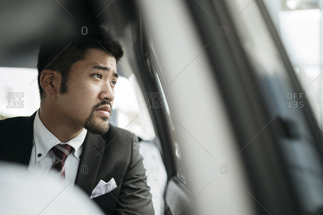 Thoughtful businessman looking through taxi window