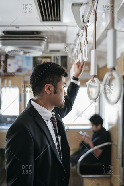 Side view of thoughtful businessman standing in train