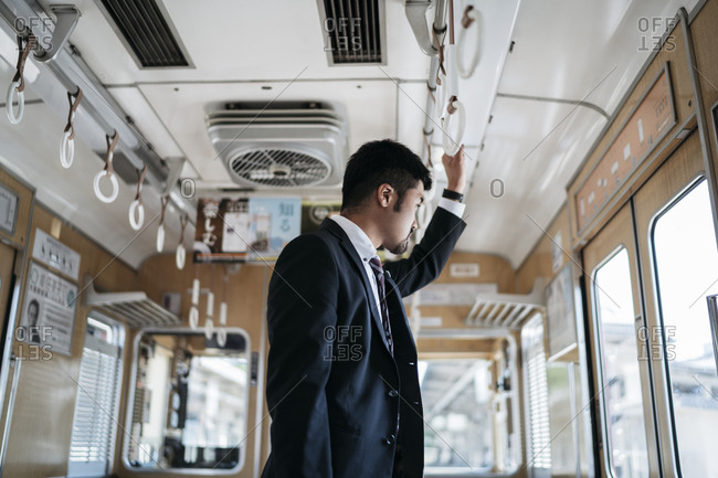 Side view of thoughtful young businessman looking through window while standing in train