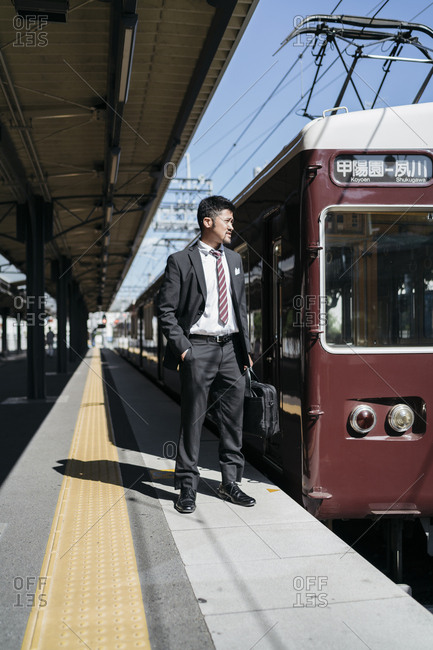 Full length of thoughtful businessman standing by train on railroad station platform