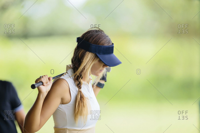 Woman with golf club at golf course