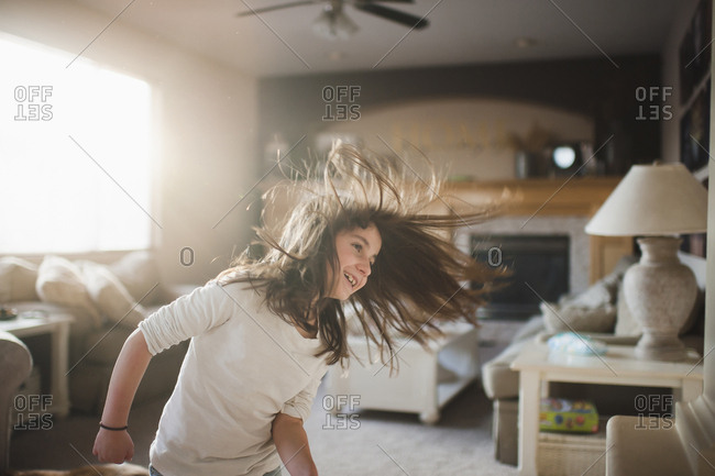 Smiling girl tossing hair while standing in living room