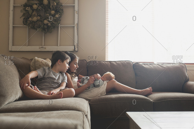 Siblings playing on baby boy while sitting on sofa at home