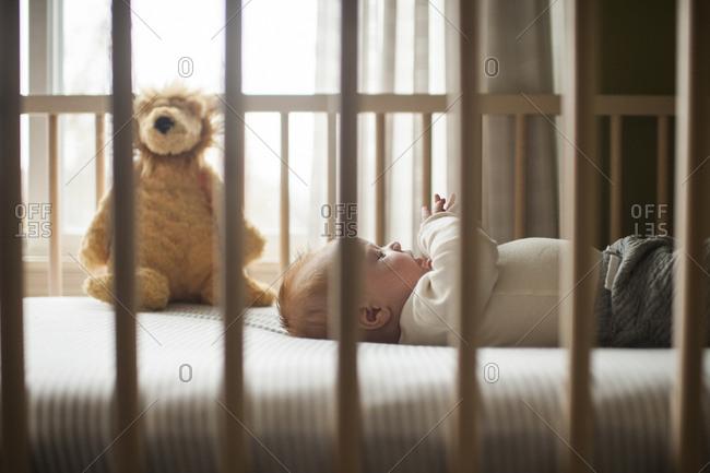 Side view of baby boy lying in crib
