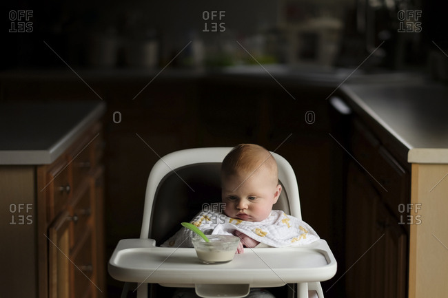 Baby boy looking at food in bowl while sitting on high chair