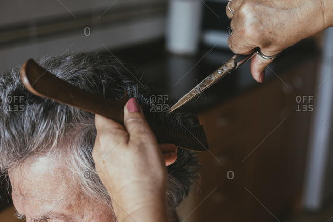 Cropped hands of female barber cutting male customer's hair