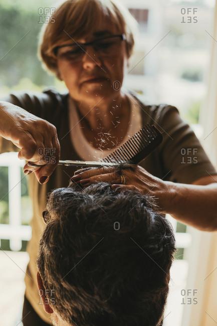 Female barber cutting hair of male customer