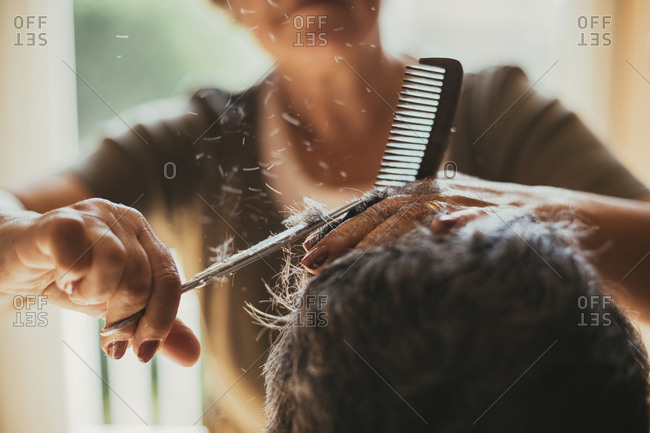 Midsection of female barber cutting male customer's hair