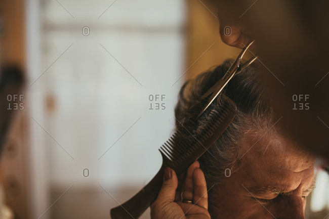 Cropped image of barber cutting male customer's hair